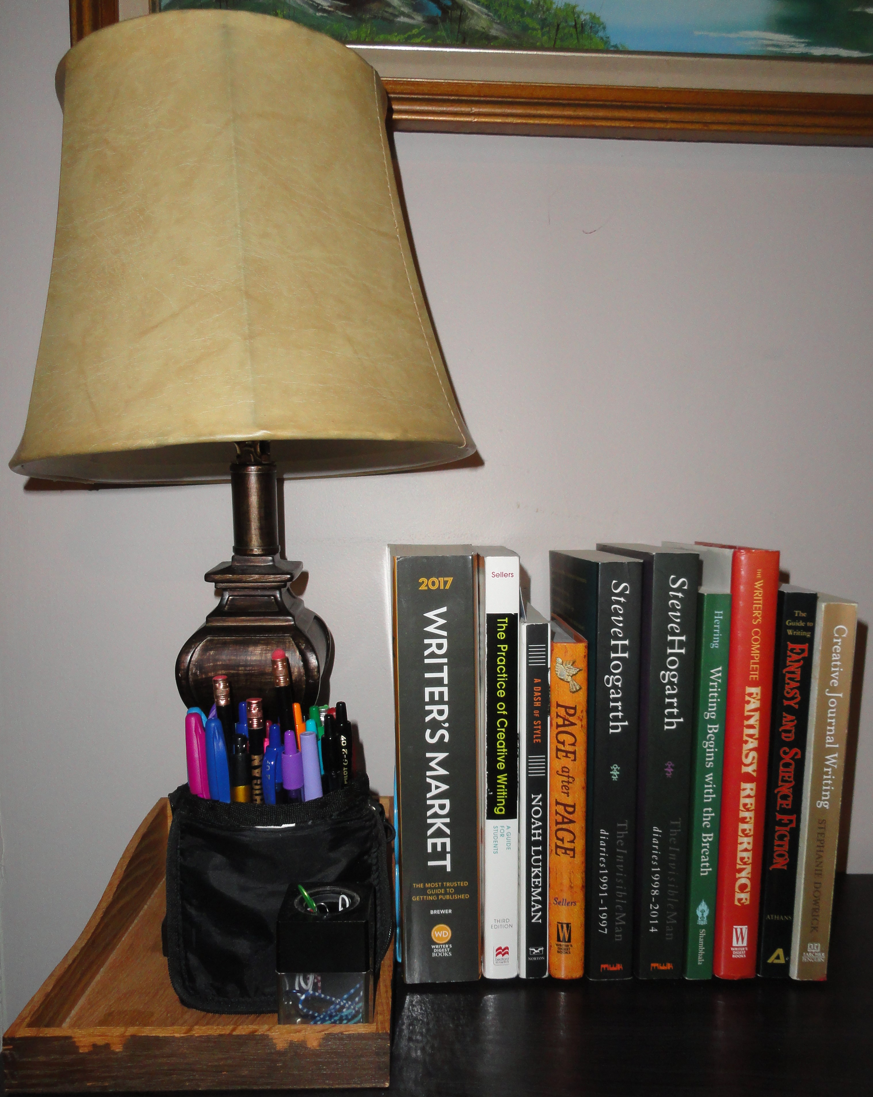 Photo of desk with lamp, writing reference books, Steve Hogarth books, writing utensils, and paper clip holder.