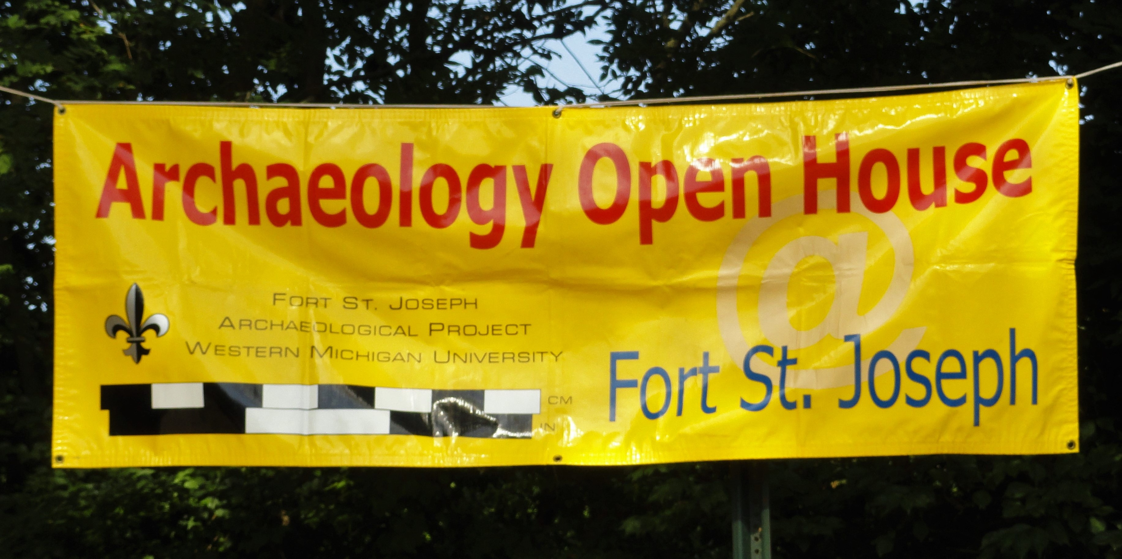 "Banner indicating where the Archeology Open House at Fort St. Joseph is being held. Text reads: ""Archaeology Open House @ Fort St. Joseph. Fort St. Joseph Archaeological Project Western Michigan University."" Image of French is one viewer's left-hand side."""