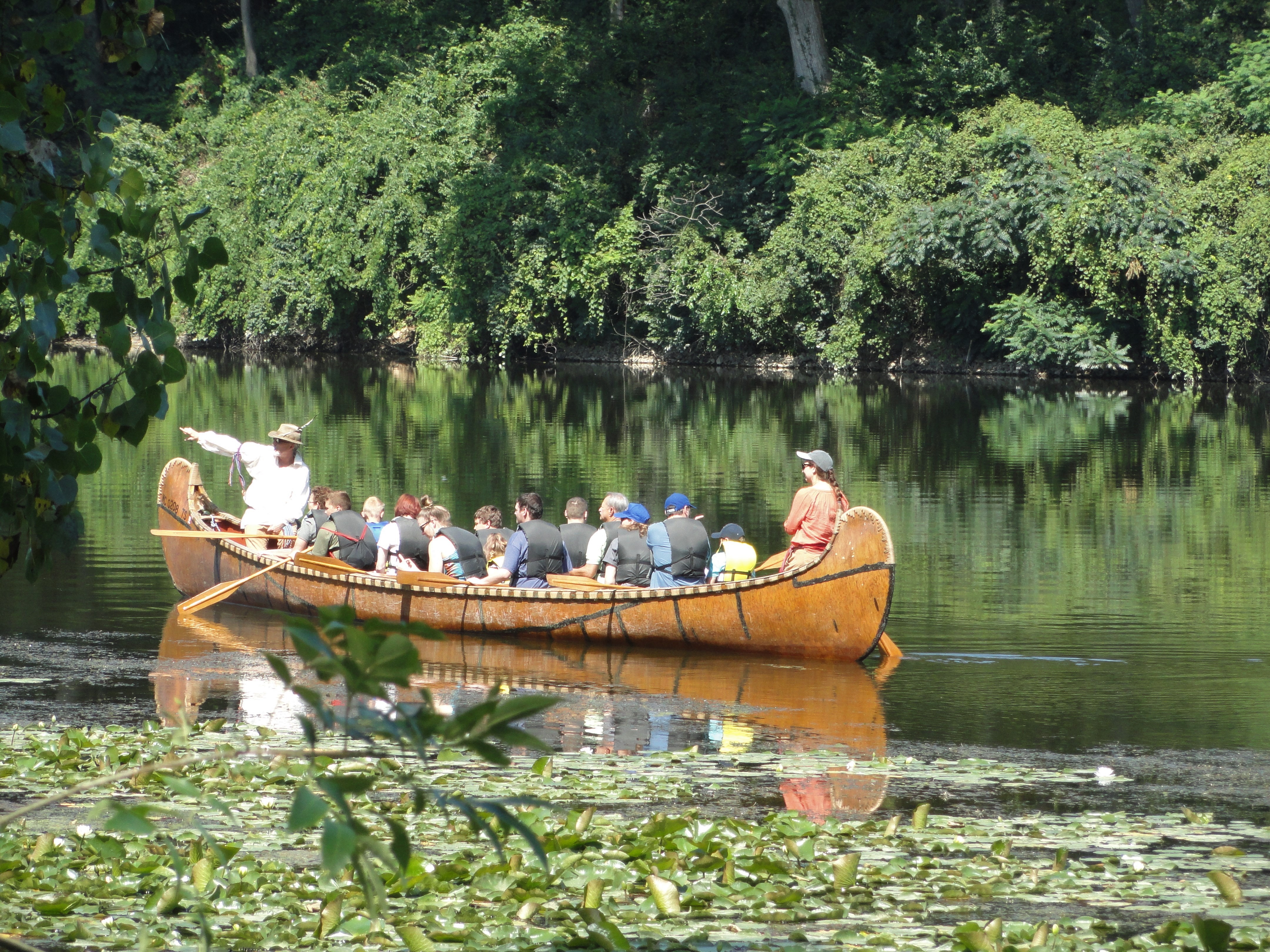People take a guided tour of the St. Joseph River in a canoe lead by a living history demonstrator.