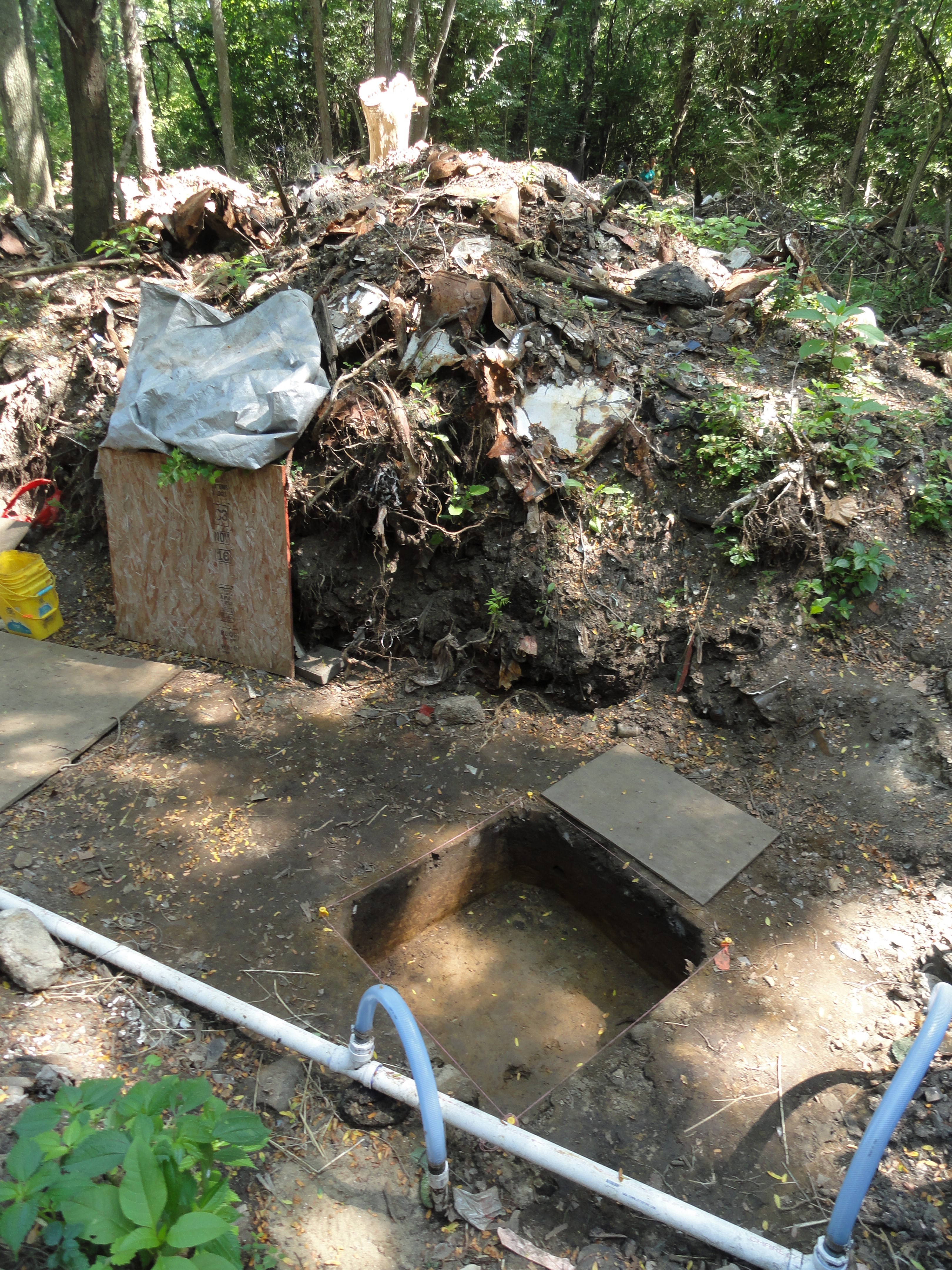 Image of trench two at Fort St. Joseph. Glass bottles, broken washing machines and other items tower above a pit dug out by students and instructors. A water removal system is in place to keep the area free of standing water during the digging season.